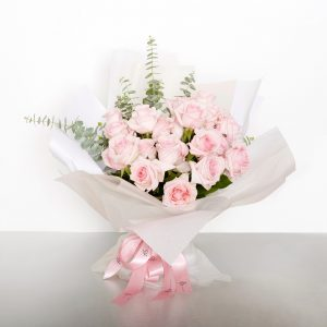 A classic bouquet of two dozen Columbian long stem pink roses accented with seasonal foliages - for soft and tender expressions. Image shows a 24 stem wrapped bouquet 55cmW x 60cmH
