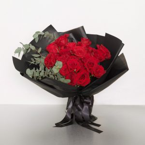 A classic bouquet of two dozen Columbian long stem red roses accented with seasonal foliages - the perfect expression of love! Image shows a 24 stem wrapped bouquet 55cmW x 60cmH