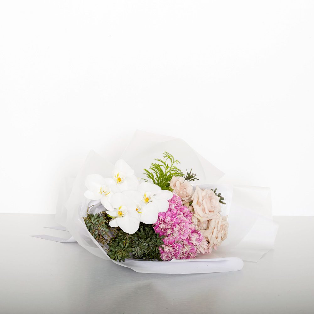 A modern bouquet of grouped classic roses,orchids, long-lasting carnations and more make for a gorgeous design for all occasions. Image shows a medium size wrapped bouquet 30cmW x 40cmL