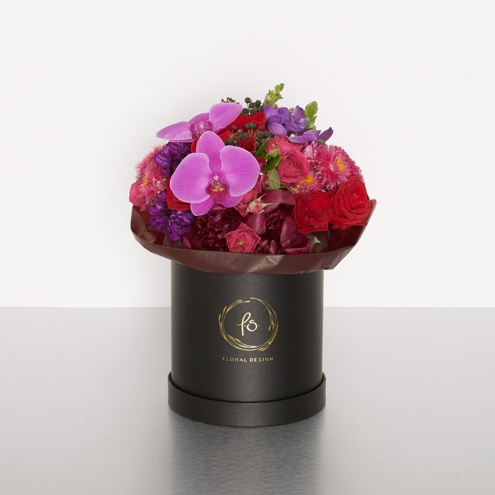 An uptown design sure to please the stylish fashionista. Rich in color,these beautiful seasonal blooms are designed into our signature cylinder boxes; perfect for grand openings, corporate gifts, and most celebrations! Image shows a medium size boxed arrangement 28cmW x 35cmH