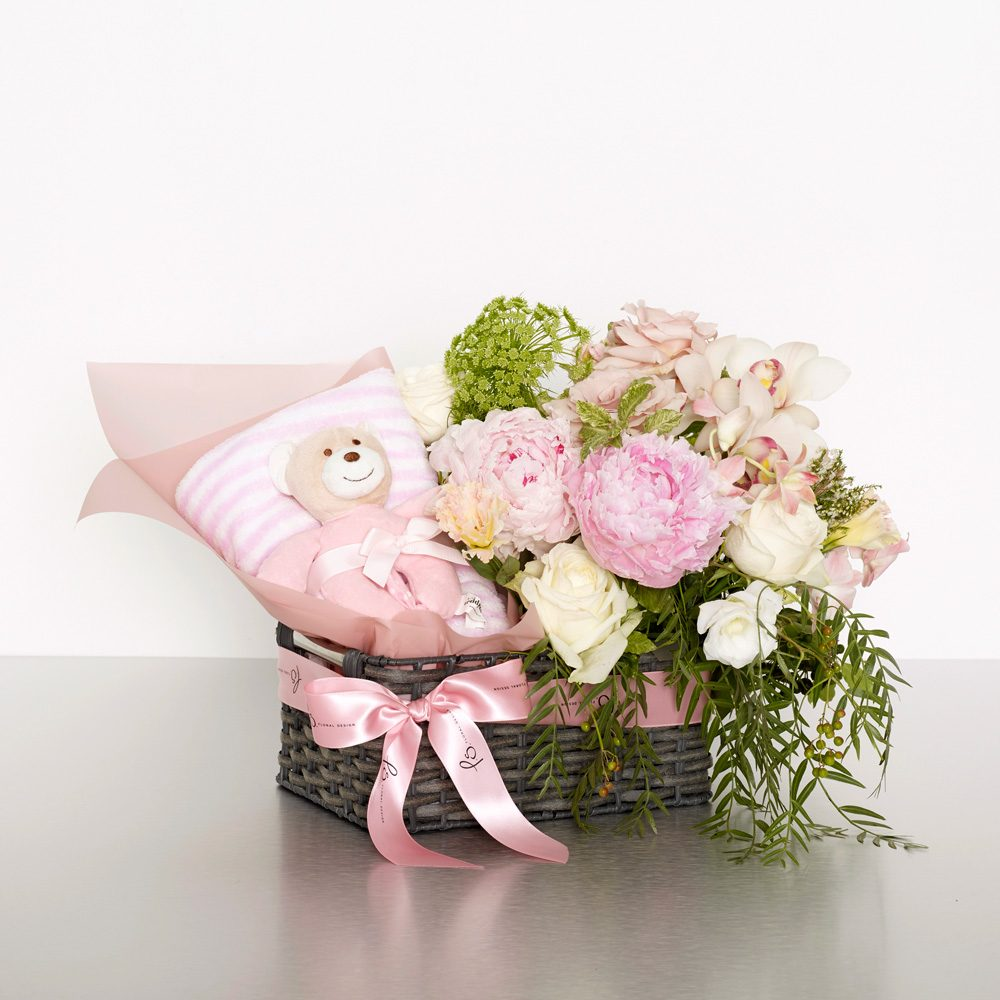 Congratulate caregivers with a gorgeous palette of pink florals. For added joy this arrangement includes a cuddly teddy and bright balloons. Image shows the small size, arranged in a basket 35cmW x 35cmH
