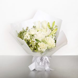 Shades of white seasonal blooms make up this stunning and classic bouquet. Suitable for most home interiors. Image shows a medium sized wrapped bouquet 30cmW x 40cmL