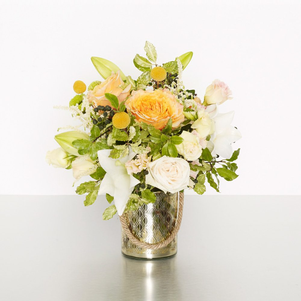 Need to brighten someone's day? Then this is the perfect design for you! A bright and sunshiny mix of white and yellow flowers in our beautiful keepsake golden spring vase. Sure to bring a smile to the room! 25cmW x 30cmH