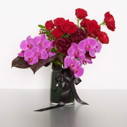 Give the gift of luxury with this richly textured vase of premium flowers. This elegant design is brimming with large-headed roses, classic orchids, and sculptural foliages. 35cmW x 40cmH